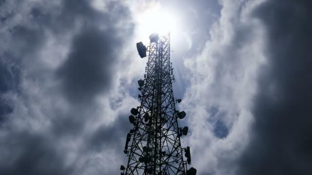 vidéos et rushes de laps de temps d'une tour de télécommunications avec le déplacement des nuages - transmission