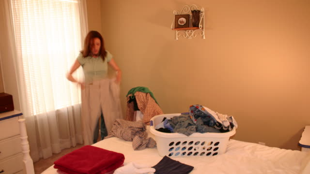 Time lapse of a young woman folding clothes HD video