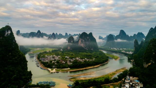 zeitraffer der luftaufnahme der li-fluss und karst bergen mit schönen wolkengebilde. in der nähe der antiken stadt xingping, yangshuo county, stadt guilin, provinz guangxi, china - guilin stock-videos und b-roll-filmmaterial