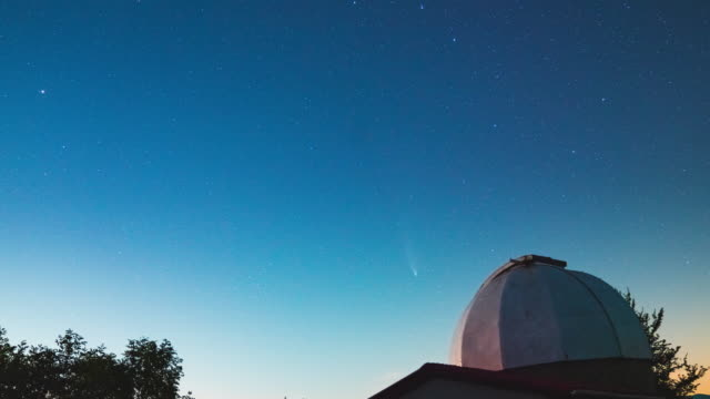 Time lapse of an observatory at night with stars and the comet Neowise in the background video