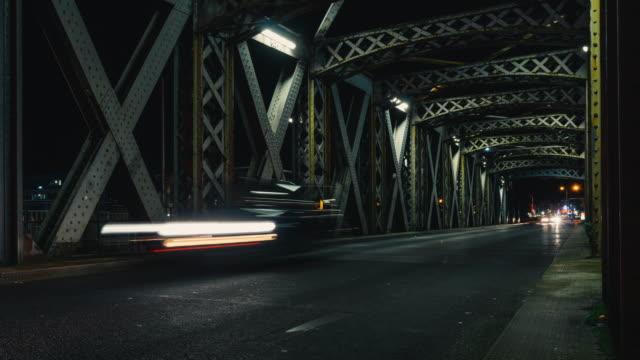 vídeos de stock e filmes b-roll de time lapse of asphalt road under the steel structure of an old metal bridge. night traffic lights in the tunnel. city life, urban scene, car light trails, transport and traffic concept. long exposure - reto descrição física