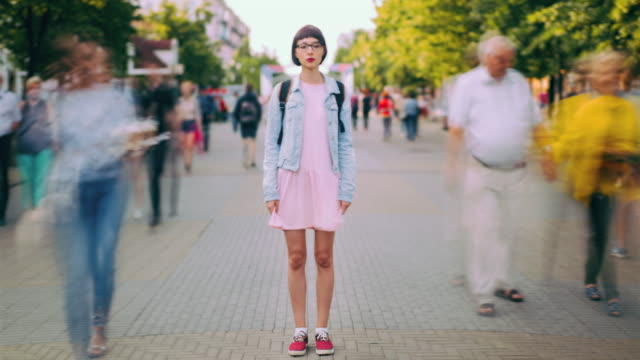 time lapse of attractive teenage girl standing in city center in busy street - stare in piedi video stock e b–roll