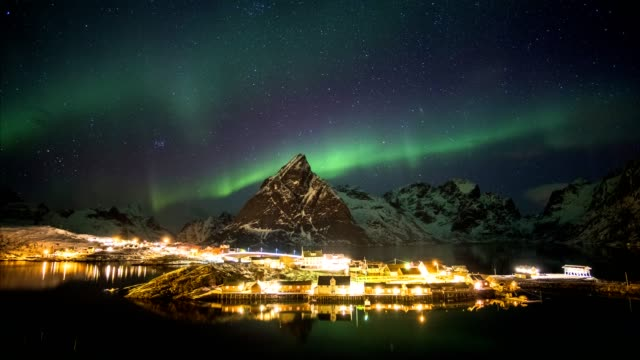 time lapse of aurora borealis dancing on mountains with fishing village - aurora boreale video stock e b–roll