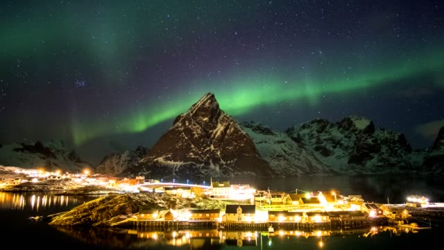 time lapse of aurora borealis dancing on mountains with fishing village - fiordo video stock e b–roll