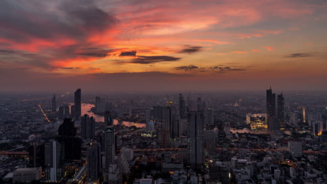 4K Time lapse of Bangkok cityscape river side with Chao praya river at the sunset time with the day to night concept