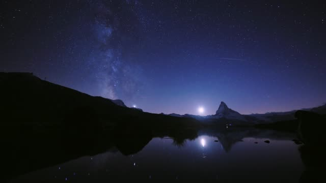 4k time lapse of beautiful sky color of the matterhorn pyramid with milky way and all the star at stellisee lake. great reflection night scene in swiss alps, zermatt, switzerland, europe - lungo video stock e b–roll