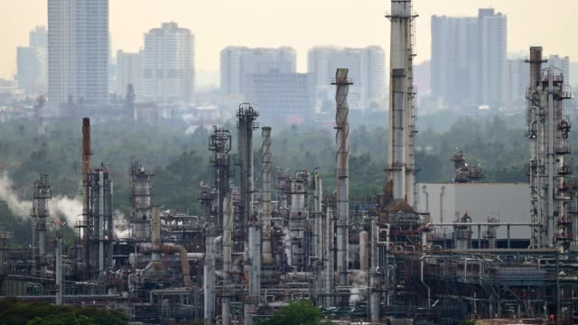 4k uhd time lapse of big oil refinery factory with large city in the background. - opec video stock e b–roll