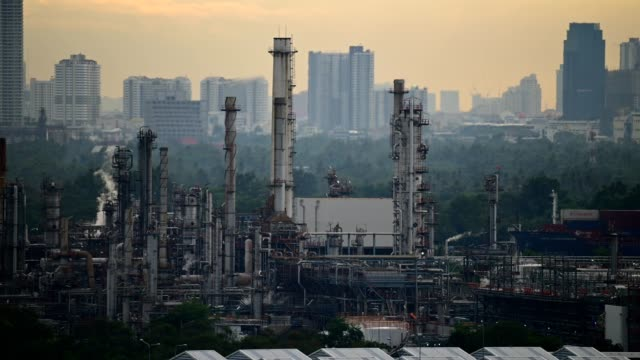 4k uhd time lapse of big oil refinery factory with large city in the background. - cartello economico video stock e b–roll
