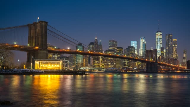 Time lapse of Brooklyn bridge and Manhattan at sunrise Panoramic view of Brooklyn bridge and Manhattan at sunrise, New York City. Time lapse of night to day transition. day stock videos & royalty-free footage