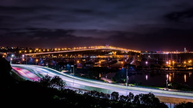 Time lapse of cars in motion on a lighted bridge and highway over the sea video