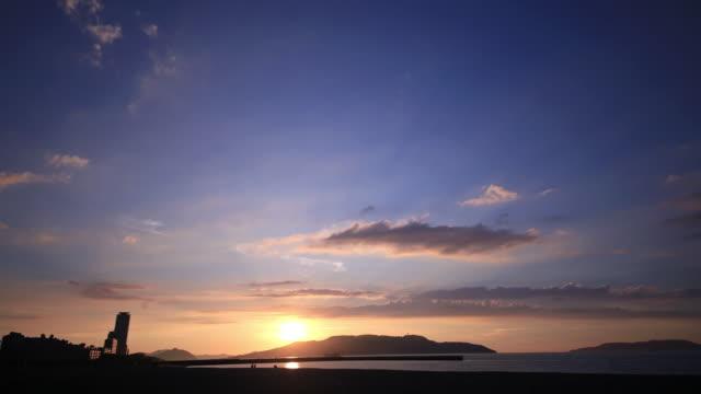 en tidsfördröjning i molnet scape och stranden i solnedgången - pink sunrise bildbanksvideor och videomaterial från bakom kulisserna