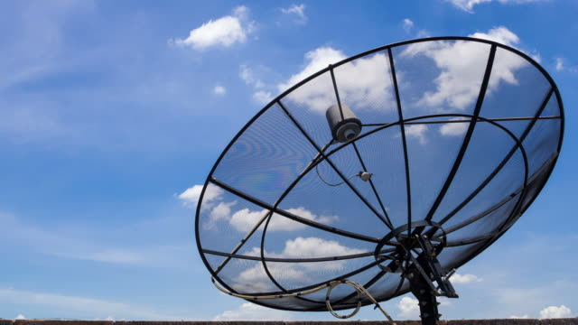 Time Lapse of clouds moving over satellite dish antennas video