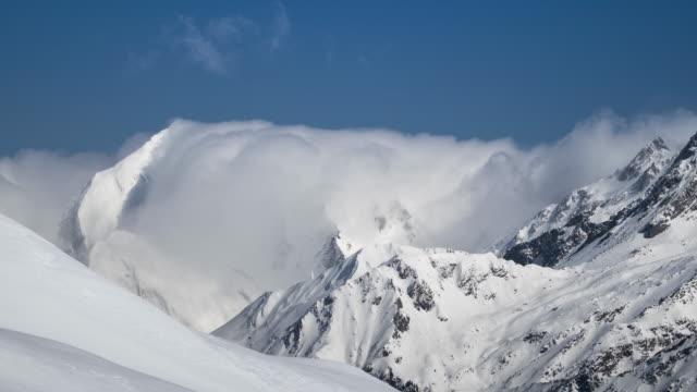 vídeos y material grabado en eventos de stock de lapso de tiempo de las nubes en montañas nevadas, el paisaje alpino - alpes europeos