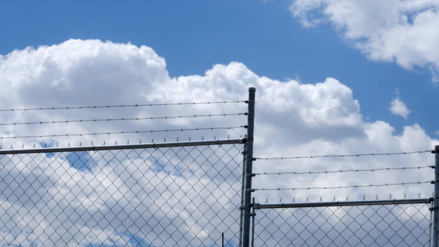 Time lapse of clouds passing over a wire fencing video