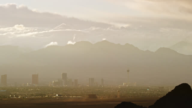 time lapse of clouds rolling over the las vegas city skyline with mountains in the background on a hazy day while dust devils blow over the desert in the foreground at sunset - smog video stock e b–roll