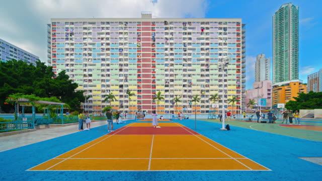 バスケットボールコートとファサードの窓の背景を持つカラフルな虹のパステルビルの時間経過。中国、香港市九龍のチェ・フン・エステートの建築建築設計。 - 吊るす点の映像素材/bロール