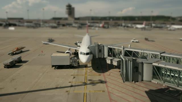 stockvideo's en b-roll-footage met time-lapse van commerciële vliegtuig permanent bij airport terminal gate - vliegveld vertrekhal
