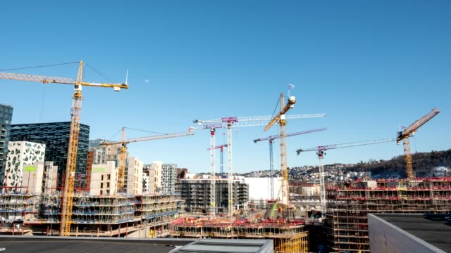 time lapse of construction building with cranes and derrick and blue sky in the city - construction filmów i materiałów b-roll