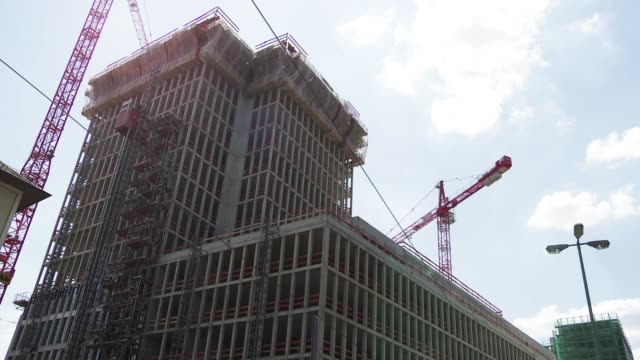 time lapse of construction cranes working on large building - movimento rapido video stock e b–roll