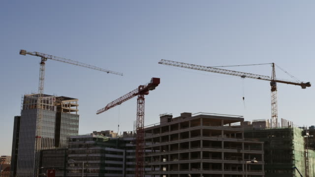 Time lapse of construction site with cranes and modern buildings