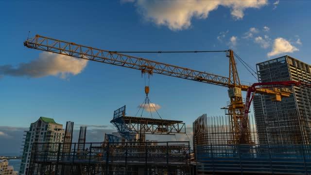 マイアミフロリダのダウンタウンにある66階建ての高級超高層ビルプロジェクトに別のフロアを追加する建設労働者のタイムラプスは、雲が過去の頭上を移動します - クレーン点の映像素材/bロール