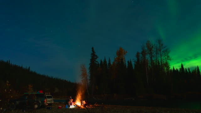 Time lapse of couple camping next to campfire under northern lights in Alaska