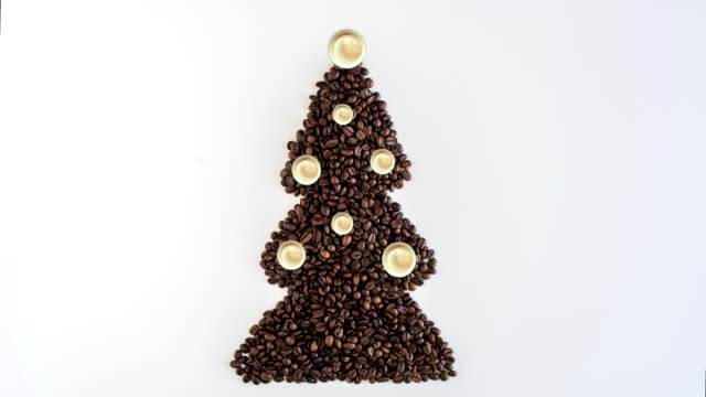 Time lapse of creative footage of christmas tree made from freshly roasted coffee beans and decorated small cups of cappuccino on white table. Winter concept. Creative. Minimalism