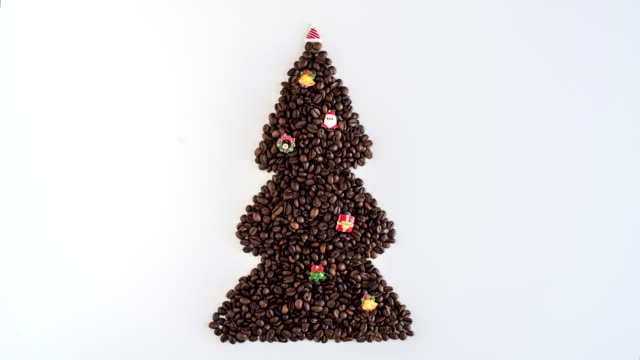 Time lapse of creative footage of christmas tree made from freshly roasted coffee beans and decorated small toys on white table. Winter concept. Creative. Minimalism