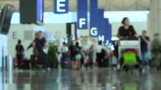 промежуток времени толпы людей, идущих с багажом в международном аэропорту. - табло вылетов и прилётов стоковые видео и кадры b-roll