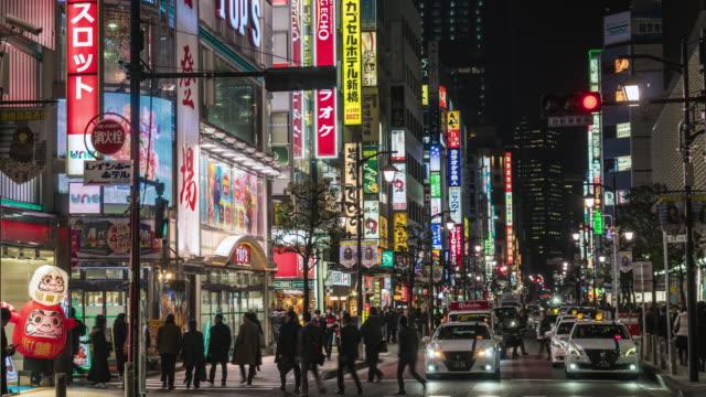 vídeos y material grabado en eventos de stock de 4k lapso de tiempo de crowd undefined personas caminando por la calle del mercado nocturno alrededor de la estación de shimbashi con tráfico de coches de la ciudad de tokio, japón. cultura japonesa y concepto de área comercial - señalización vial