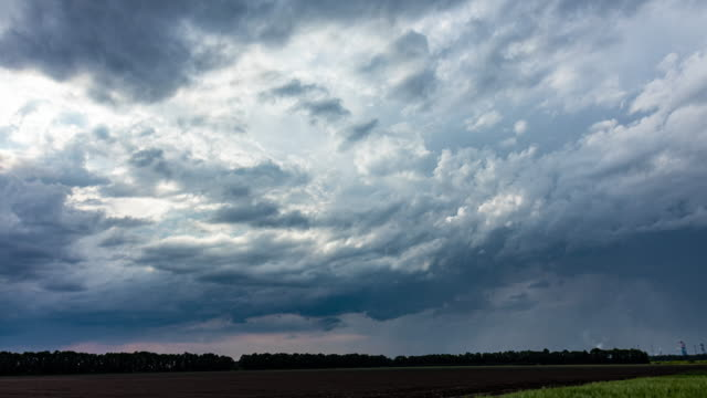 Time lapse of dramatic rain cloud rolling. Light rays shining through clouds. video
