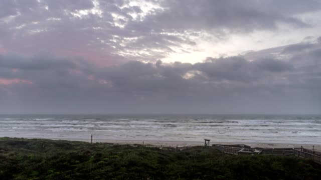 Time lapse of Early Sunrise Clouds Moving inland from Sea Over Texas Beach