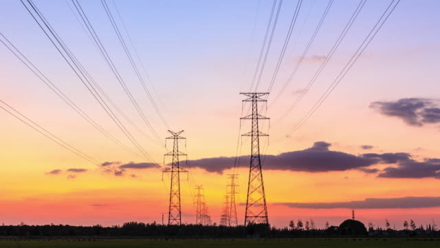 time lapse of electric high voltage pylon.silhouette of electricity power lines at sunset. - cavo componente elettrico video stock e b–roll
