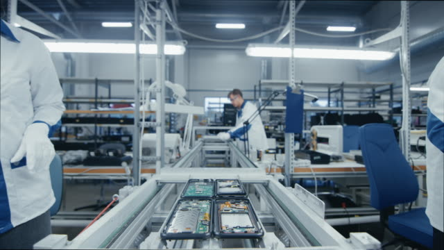 time lapse of electronics factory workers assembling smartphone circuit boards by hand while they move on the assembly line. high tech factory facility. - produkować filmów i materiałów b-roll