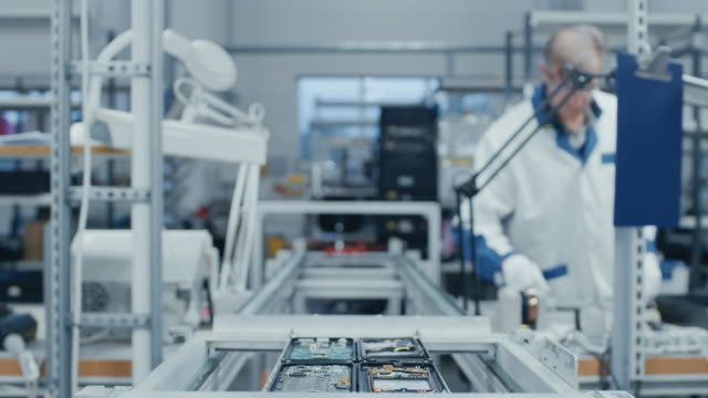 time lapse of electronics factory workers assembling smartphone circuit boards by hand while they move on the assembly line. high tech factory facility. - chip komputerowy filmów i materiałów b-roll