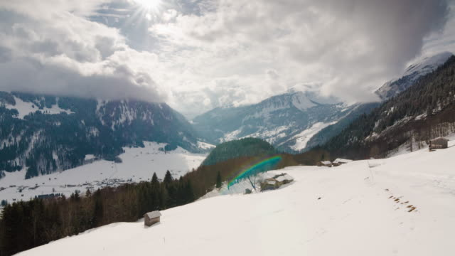 Time lapse of epic clouds over an alpine valley with mountain huts in foreground video