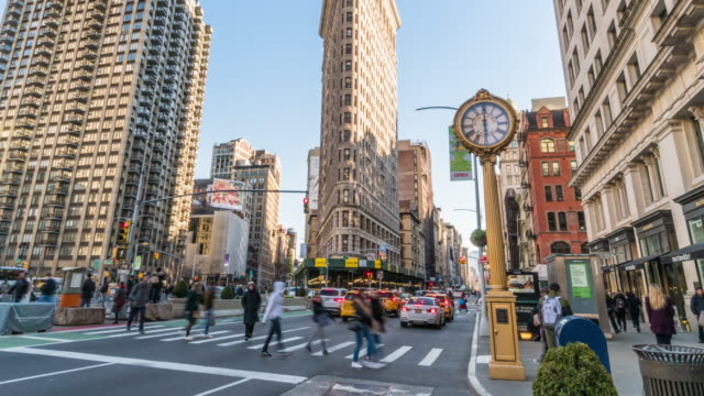 4K Time lapse of Flatiron Building with pedestrians and traffic road intersection in rush hour among modern buildings, Manhattan, New York City, United States. Business and Transportation concept