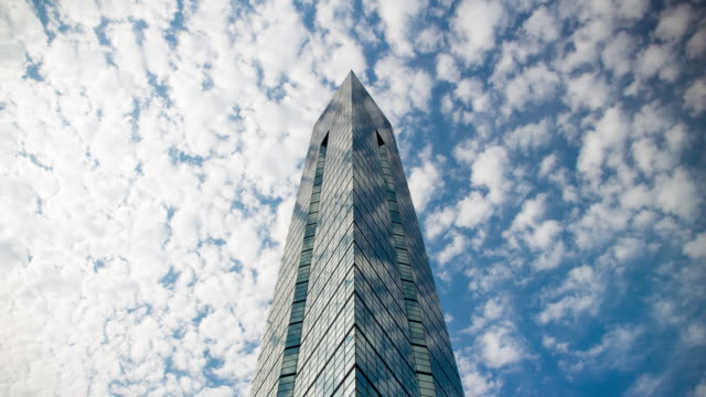 Time lapse of flowing clouds over Fukuoka tower in blue sky. Urban landscape in Japan