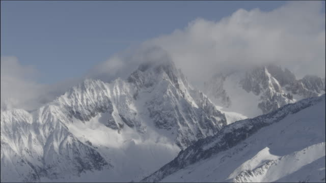 time lapse of fog curling around mountain in chamonix, france - monte bianco video stock e b–roll