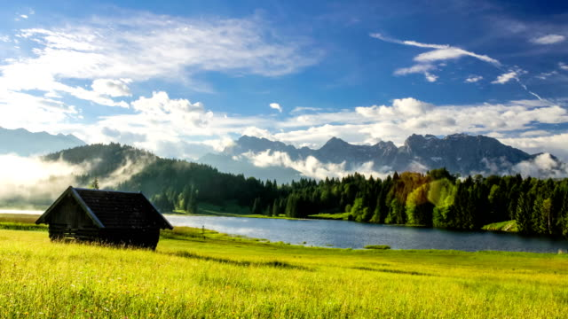 Time lapse of fog floating over lonely house in the meadow at beautiful morning sunrise at mountain lake Geroldsee in Bavarian Alps Germany