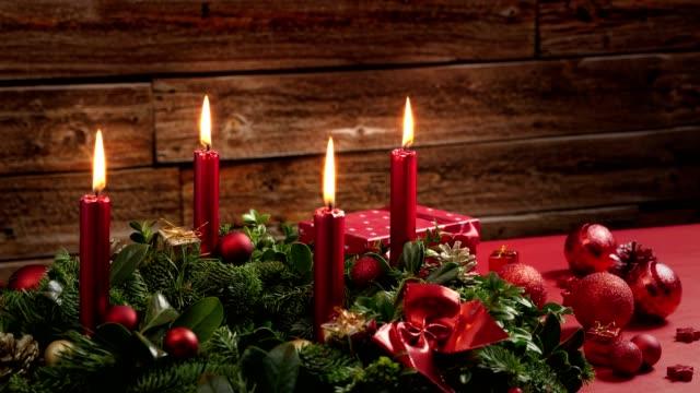 Lapso de tiempo de cuatro velas rojo ardientes en una corona de Adviento con la decoración festiva - vídeo