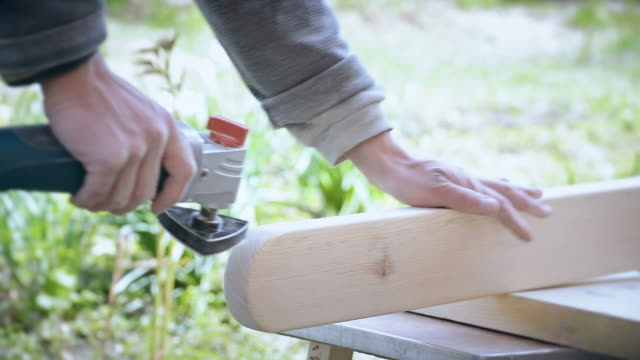 time lapse of grinding a wooden plank with an orbital detail sander - levigatrice video stock e b–roll