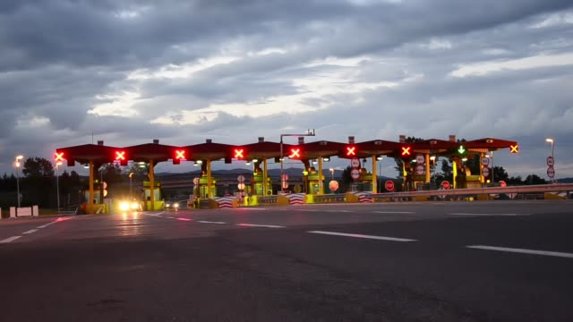 Time lapse of Highway Car Paytoll at sunrise, Night lights and Autos passing through toll booths, pay for using highway and motorway