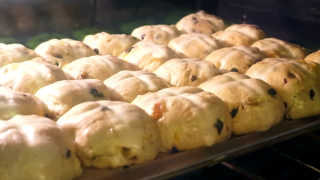 Time lapse of hot cross buns rising in oven Looking through glass oven door as hot cross buns bake.  Gas flame can be seen turning on and off to maintain temperature during time lapse sequence. bun bread stock videos & royalty-free footage