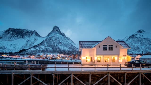 Time lapse of House on fishing village glowing with mountain at dusk Time lapse of House on fishing village glowing with mountain at dusk. Mefjord Brygge, Troms, Norway polar climate stock videos & royalty-free footage