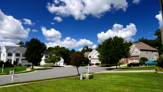 vídeos de stock e filmes b-roll de time lapse of idyllic suburbs with homes and rolling cumulus clouds - suburbano