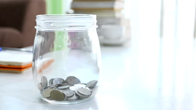 time lapse of increase money coins in the glass jar - risparmi video stock e b–roll