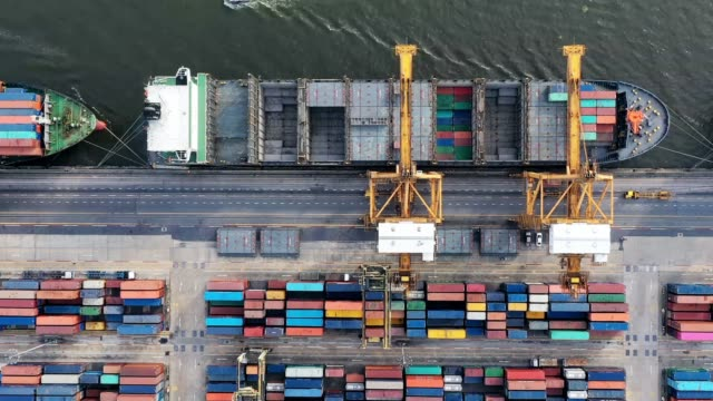 vídeos de stock e filmes b-roll de time lapse of industrial logistic port view from drone point of view - docas