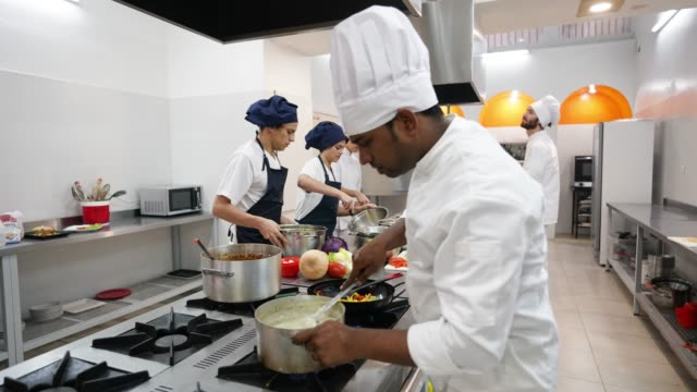 Time lapse of kitchen staff working on different tasks at an industrial kitchen preparing orders to serve Time lapse of kitchen staff working on different tasks at an industrial kitchen preparing orders to serve at the restaurant commercial kitchen stock videos & royalty-free footage