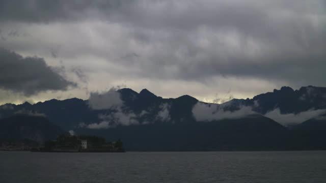 vídeos de stock e filmes b-roll de time lapse of lago maggiore on a cloudy day and the isola bella - lago maggiore
